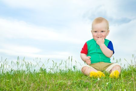 liitle baby sit on grass with hand in mouth under blue sky photo