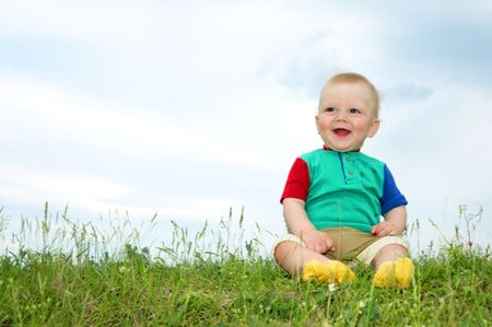 little baby sit on green grass under sky photo