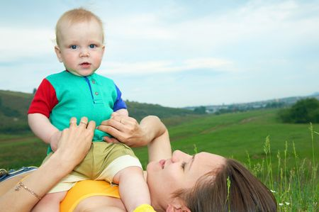 mother with baby on green grass under sky photo