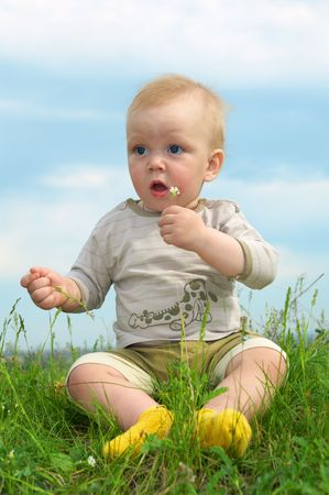 little baby  on green grass with flower photo