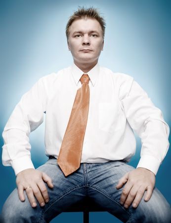 young businessman in white shirt and orange tie on blue background photo