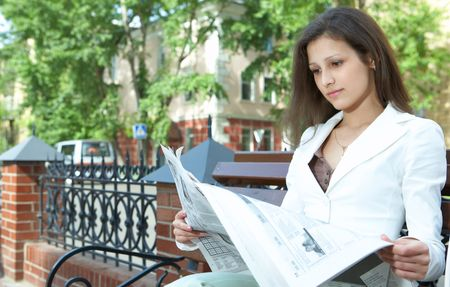pretty business woman reading the newspaper photo