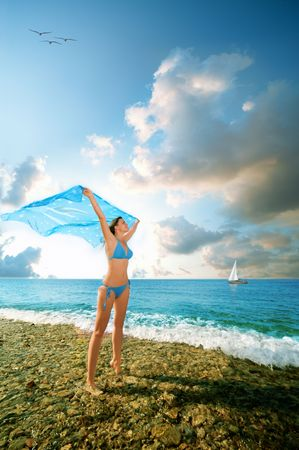 young beauty woman stand on sea beach with kerchief photo