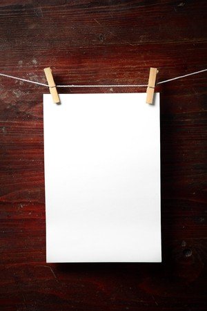 attach: Photo paper attach to rope with clothes pins on wooden background