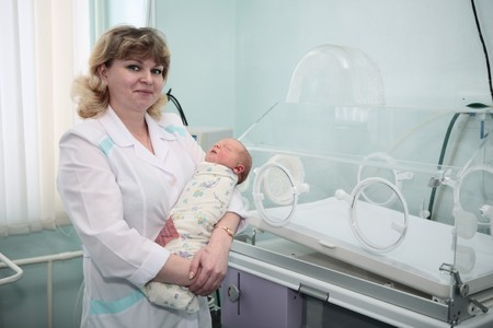 newborn in childbearing centre and doctor photo