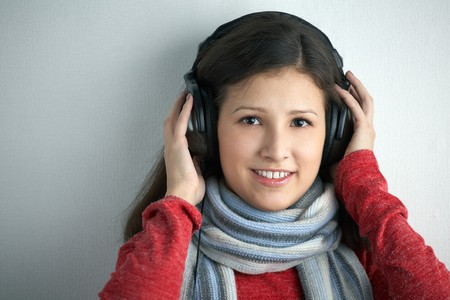 beauty young woman with headphones on gray background photo