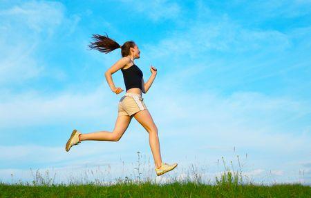 donna eseguito su erba verde sotto il cielo Archivio Fotografico