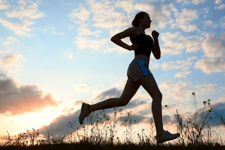 jogging shoes: Silhouette woman run under blue sky with clouds and sun Stock Photo