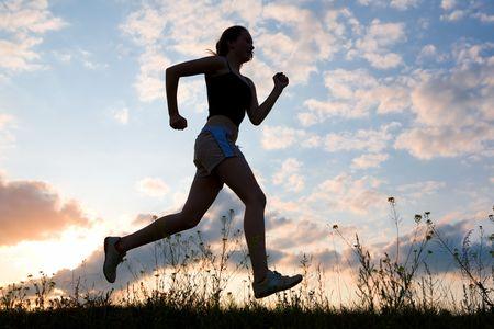 sun track:  silhouette woman run on sunrise Stock Photo