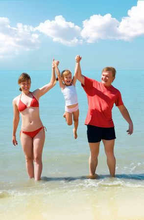 young family having fun on the beach photo