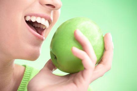 donna giovane bellezza con la mela su sfondo verde