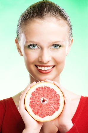 young beauty woman with grapefruit on green background photo