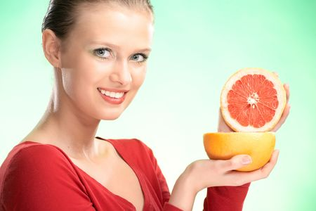 young beauty woman with grapefruit on green background Stock Photo - 5526756