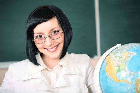 young teacher woman on green board in classroom photo