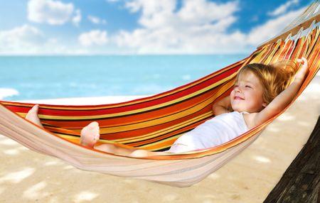 hamaca: ni�o relajarse en una hamaca en la playa de mar Foto de archivo