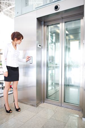 people in elevator: business woman push button of  elevator