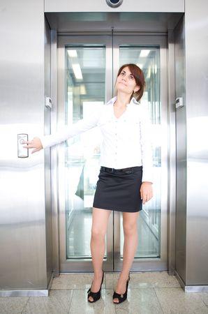 businesswear: business woman push button of  elevator