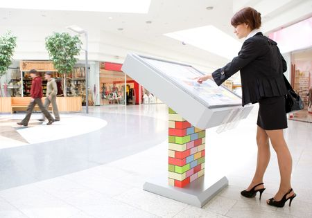 interactive: young business woman select  goods on interactive display