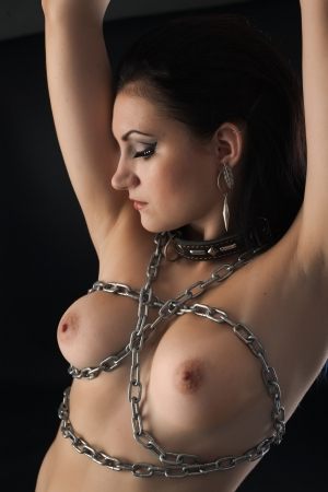 young naked woman in chain on black background photo
