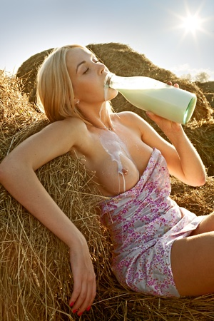 beautiful woman with bare breasts sitting on hay and drinking milk Stock Photo