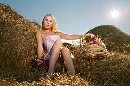beautiful woman sitting on the hay with a basket of fruit and a pitcher of raspberry photo
