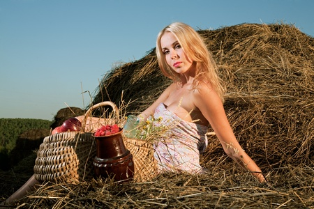 beautiful woman sitting on the hay and eat raspberries photo