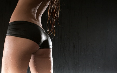 nude woman posing: beauty woman wet ass on black background Stock Photo