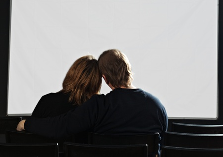 back seat: couple in cinema with white screen Stock Photo