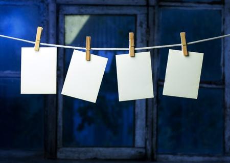 attach?: papel fotogr�fico de cuatro adjuntar a cuerda con pernos de ropa en el fondo de la ventana Foto de archivo