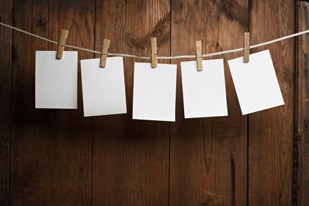 adjuntar: papel fotogr�fico de cinco adjuntar a cuerda con pernos de ropa sobre fondo de madera Foto de archivo