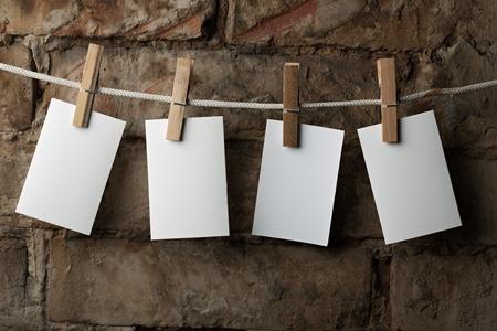 adjuntar: papel fotogr�fico de cuatro adjuntar a cuerda con pernos de ropa sobre fondo de ladrillo