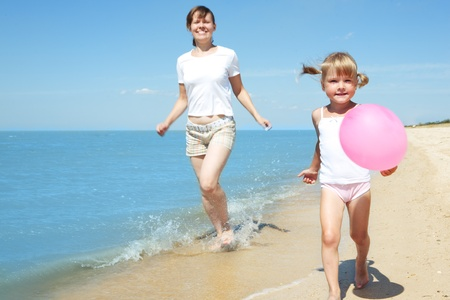 mother and child run on sea beach Stock Photo - 8850029