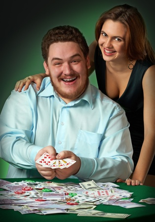 Poker players in casino with cards and chips on green background photo
