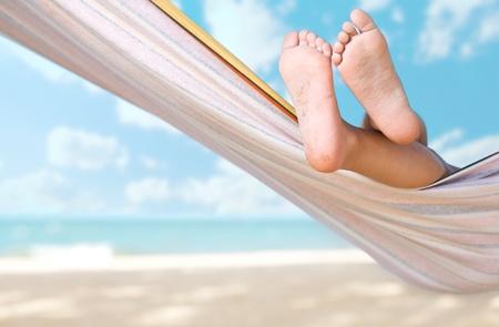 hamaca: piernas de ni�o en hamaca en la playa de mar Foto de archivo