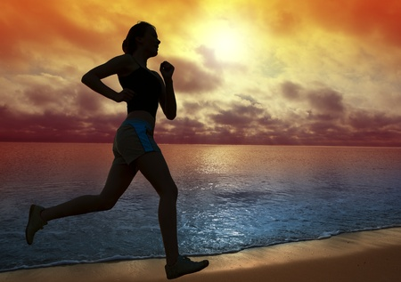 Beautiful young woman running on a beach at sunset  photo