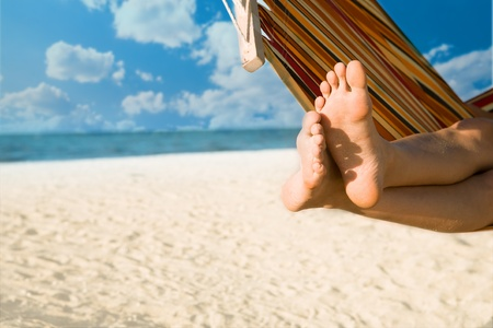 beach feet: woman legs on hammock at sea beach Stock Photo