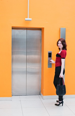 people in elevator: woman with elevator in orange color