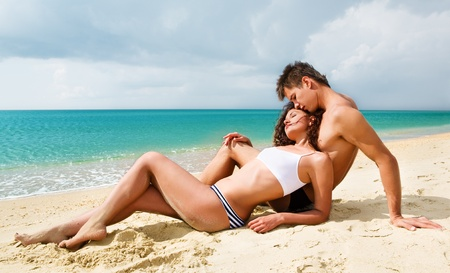 heterosexual couples:  Attractive young couple relaxing on the beach Stock Photo