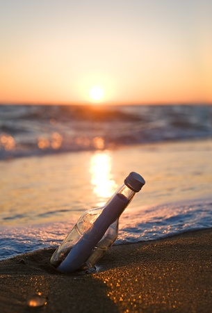 Message in a Bottle on sea beach photo