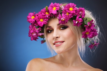 beauty woman portrait with wreath from flowers on head blue background Stock Photo
