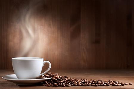 granos de cafe: Copa caliente de ciffee sobre fondo marr�n Foto de archivo