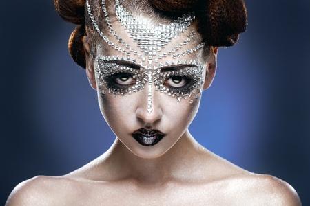 schoonheid vrouw make-up met kristallen op gezicht op blauwe achtergrond
