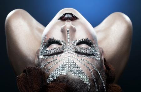 schoonheid vrouw make-up met kristallen op het gezicht op een blauwe achtergrond