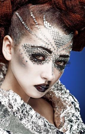 glitter makeup: maquillaje de mujer de belleza con cristales de cara sobre fondo azul