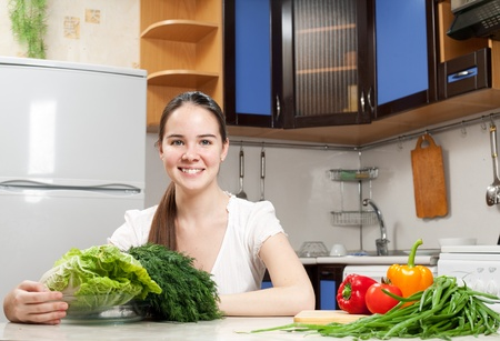 young beautiful caucasian woman in the kitchen with vegetable photo