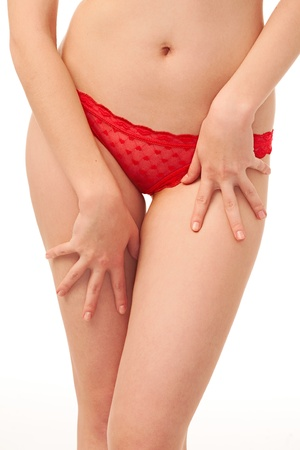 red panties: woman stomach and red panties over white background