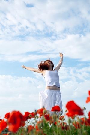 low angle views: mujer de belleza en el campo de amapolas en vestido blanco Foto de archivo