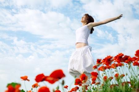 beauty woman in poppy field in white dress