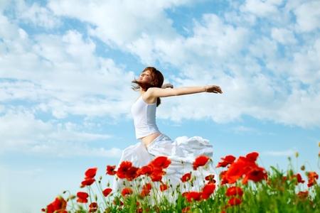 femme de beauté dans le champ du pavot en robe blanche