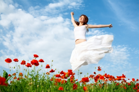 beauty woman in poppy field in white dress
